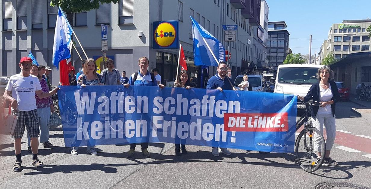 """Transparent mit der Aufschrift: """"Waffen schaffen keinen Frieden."""""""